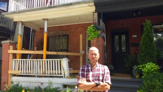 Jack Krasowski stands in front of the homes. One is his, the other is propped up by support beams placed by the city.